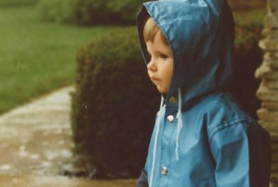 A one year old girl in a raincoat.