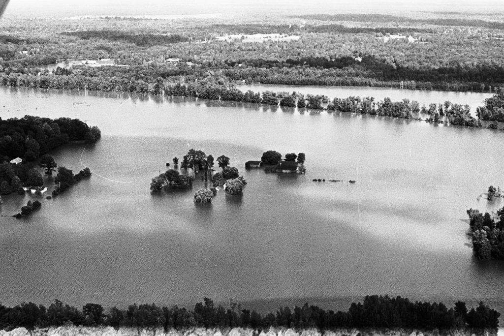 An aerial photo of a flooded farm with water all the way up to the house.