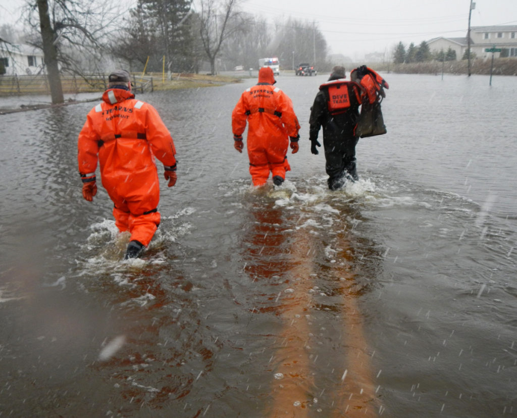 A rescue team in jumpsuits carrying life jackets through the flood waters on a road that is completely underwater.