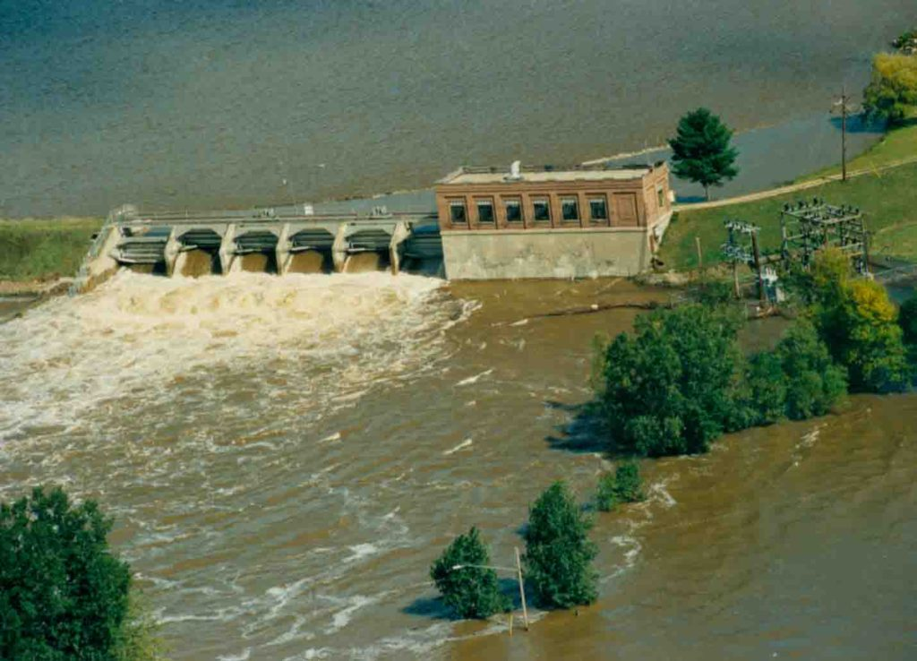 An aerial photo of the Sanford Dam with water rushing past and flooding the area.