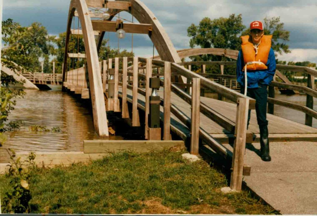 A man in a life jacket standing on a bridge with water nearly reaching the bottom of the bridge.